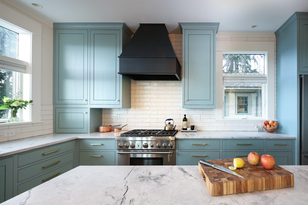 Gas stove with a custom, painted range hood and cabinets by Renew Woods.